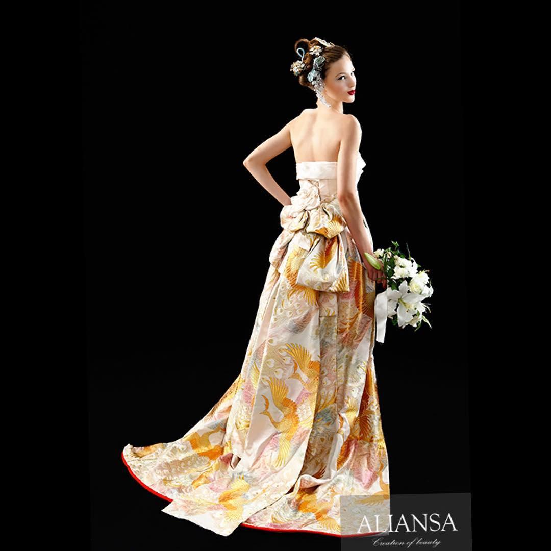 白の色打ち掛け。  孔雀柄がペールトーンの虹色に輝くドレス。  内側の白無垢も同じ柄の色無垢。  オーバースカートを外せば、ウエディングドレスとしても着られます。  白無垢の織柄は光で浮き上がる美しい生地。  白無垢の中にも一部に虹色がキラキラ。  さりげなさがステキなドレスです。